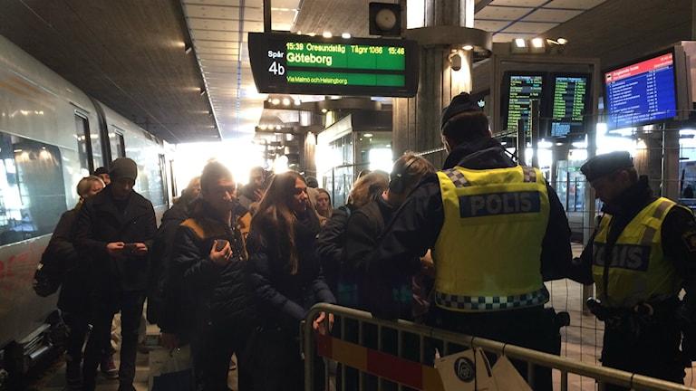 Bilden visar passagerare som klivit av tåget från Danmark på Hyllie station i Malmö. De köar framför två poliser som gör gränskontroll. På en skylt ser man att tåget är försenat. Foto: Anna Bubenko/Sveriges Radio.