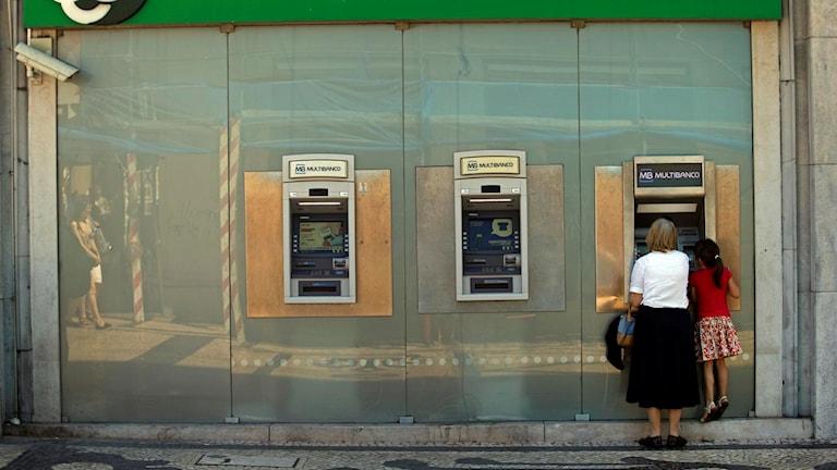 Människor köar till bankomat. Arkivfoto: Francisco Seco/AP.