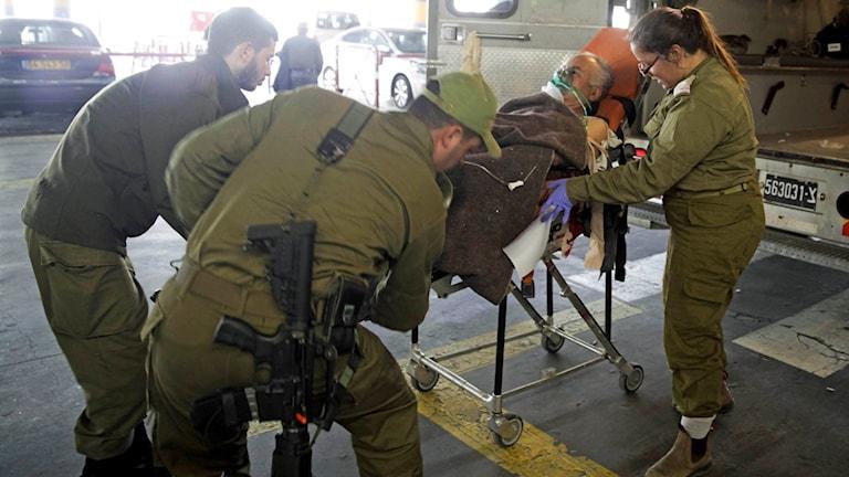 Israeliska soldater lastar ur en palestinsk man som skadades när han försökte hindra den palestinska kvinnan från att knivhugga en soldat på Västbanken.