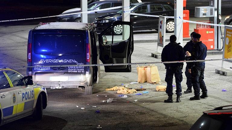 Polis och avspärrningar kring en minibuss med kulhål i på en bensinmack i Fittja.