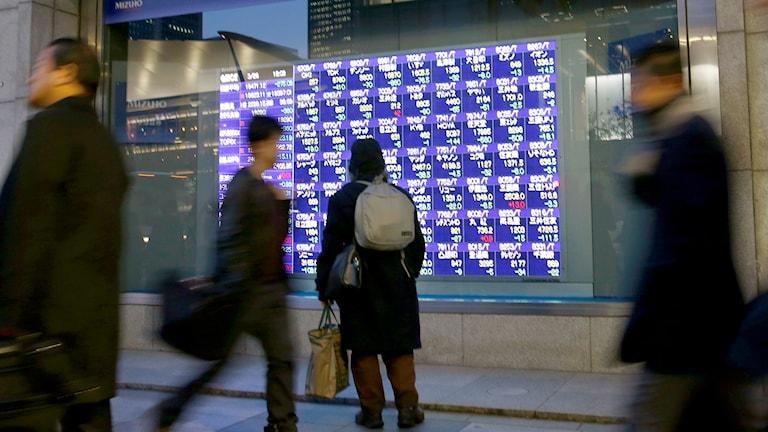 En tokyobo tittar på börsskärmar i Tokyo.