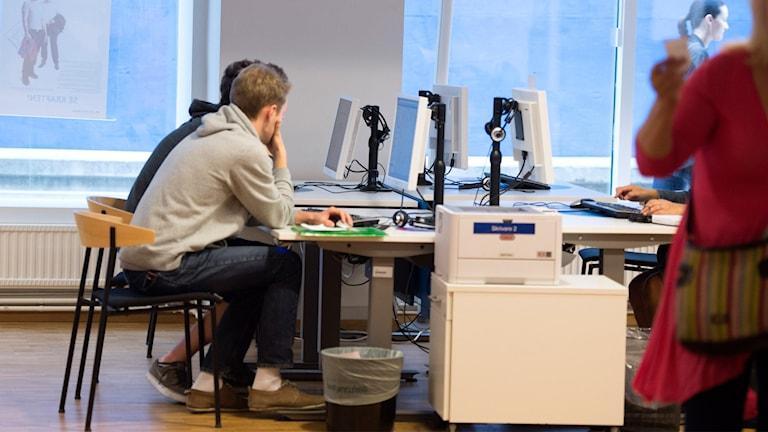 Arbetssökande vid skrivbord på Arbetsförmedlingen.