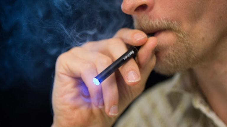 Man röker E-cigarett