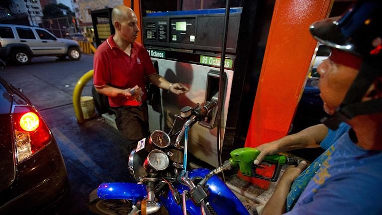 En man tankar sin motorcykel på en bensinstation i Venezuelas huvudstad Caracas.
