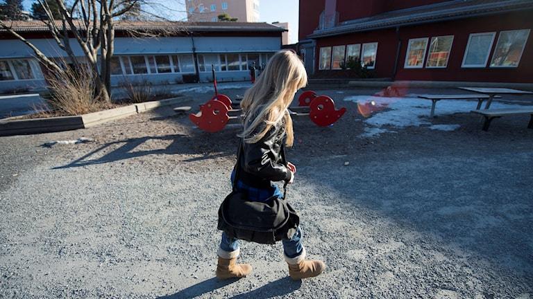 Flicka promenerar ensam över en skolgård. Foto: Fredrik Sandberg/TT.