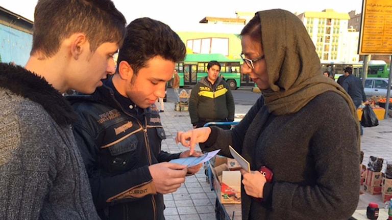 En ung iransk kvinna delar ut flygblad inför valet.