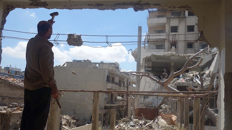 Man står och håller upp hammare i trasig byggnad i Syrien.