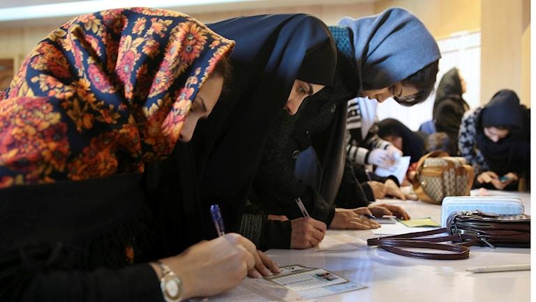 Tre kvinnor står vid ett bord och skriver.