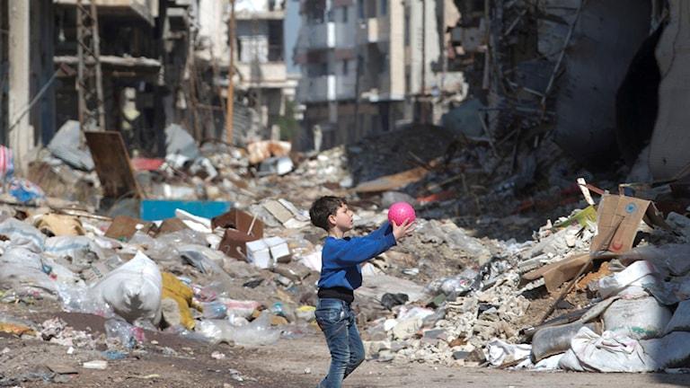 En pojke leker med en boll bland ruiner i staden Homs, Syrien Foto: Hassan Ammar/AP