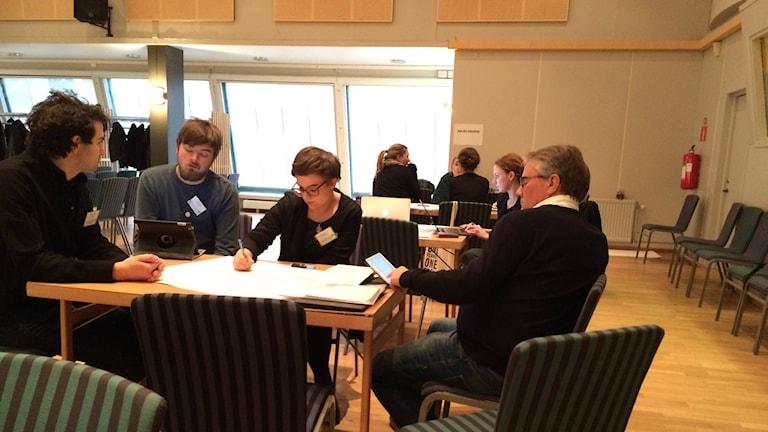 Bilden visar några miljöpartister som sitter och diskuterar runt ett bord i en konferenssal på Kockum Fritid, Malmö, under Miljöpartiets dialogkonferens. Foto: Anna Bubenko/Sveriges Radio.
