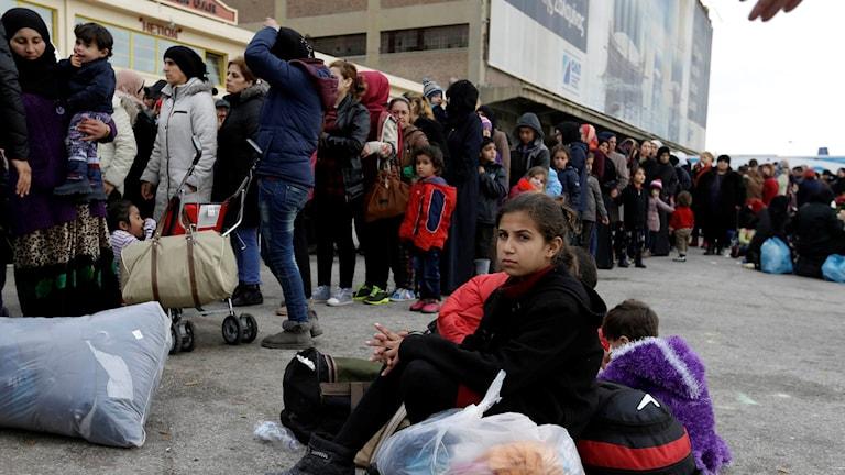 Flyktingar och migranter köar för att få mat av hjälporganisationer efter att ha anlänt till hamnen Pireus i Aten på måndagen.