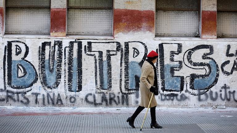 """Förbipasserande framför graffitin """"Buitres"""", som på spanska anspelar på """"gam-fonderna"""" och disputen mellan Argentina och de amerikanska långivarna."""