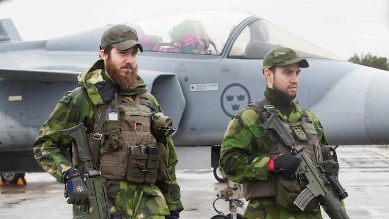 Soldater framför ett JAS Gripen-plan deltar i den internationella flygövningen Arctic Challenge Exercise 2015 i Luleå.