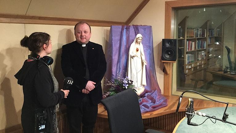 Präst som blir intervjuad i en radiostudio med en madonna-staty.