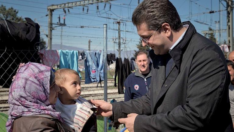 Apostolos Tzitzikostas lokal guvernör i norra Grekland talar med en migrant.