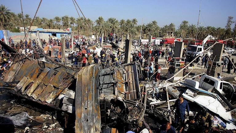 Människor vid platsen för en sprängdåd i Irak.