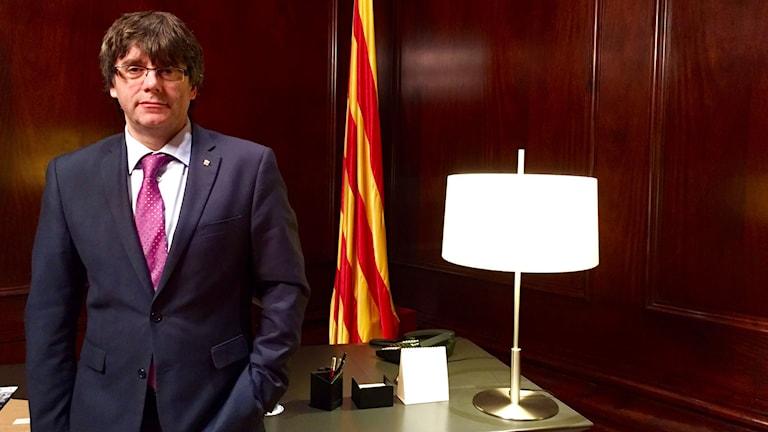 Sorglig man i kostym i kontor med katalansk flagga