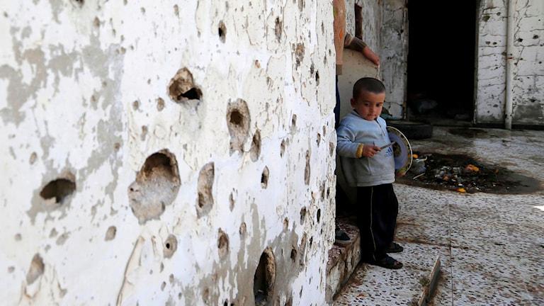 Liten pojke i ett förstört hus, väggarna är fulla av kulhål.