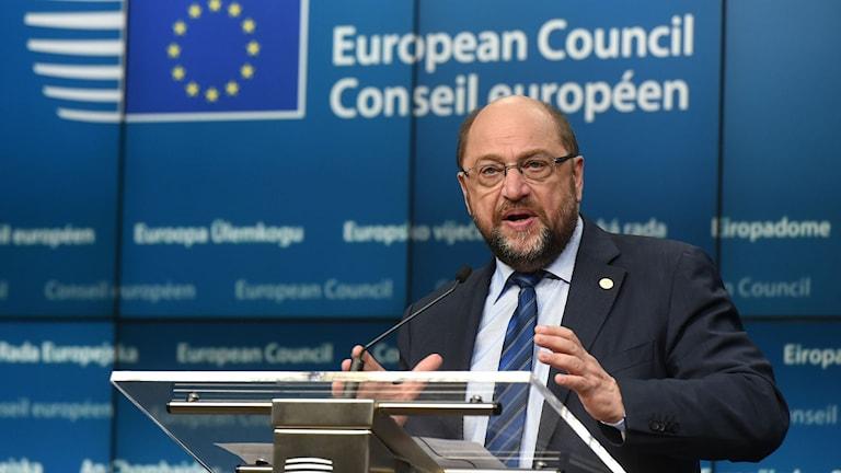 Man i talarstol med EU-flagga i bakgrunden.