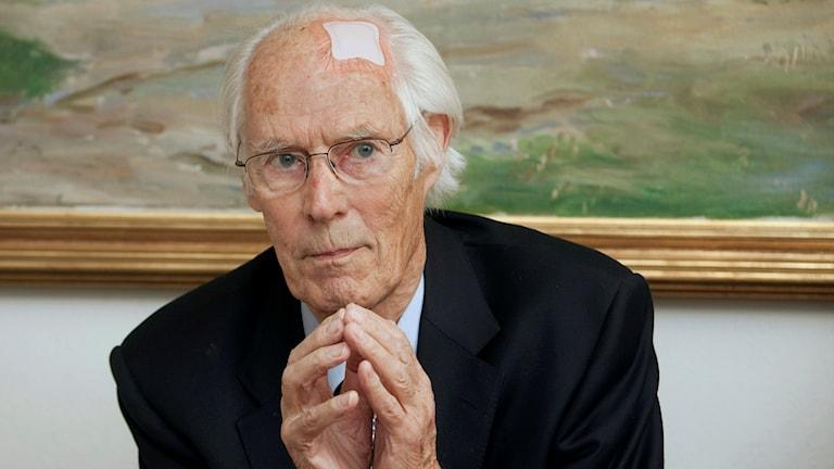 En vithårig äldre man i glasögon