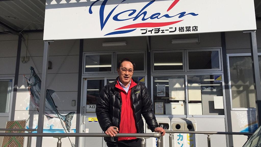 Japansk man i röd tröja och svart jacka framför mataffär