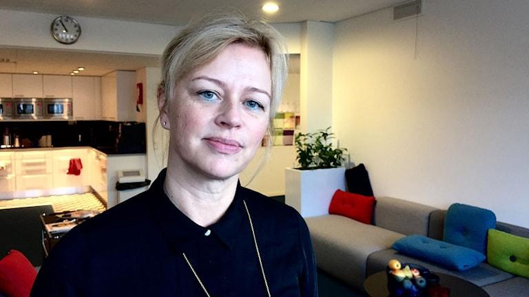 kvinna med blont hår i vitt rum med färgglada kuddar