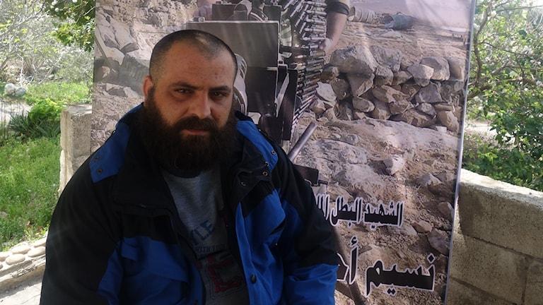 Asif Ahmad Saleh är soldat i syriska elitstyrkor, han sitter framför porträtt av sin bror som nyligen dödades.