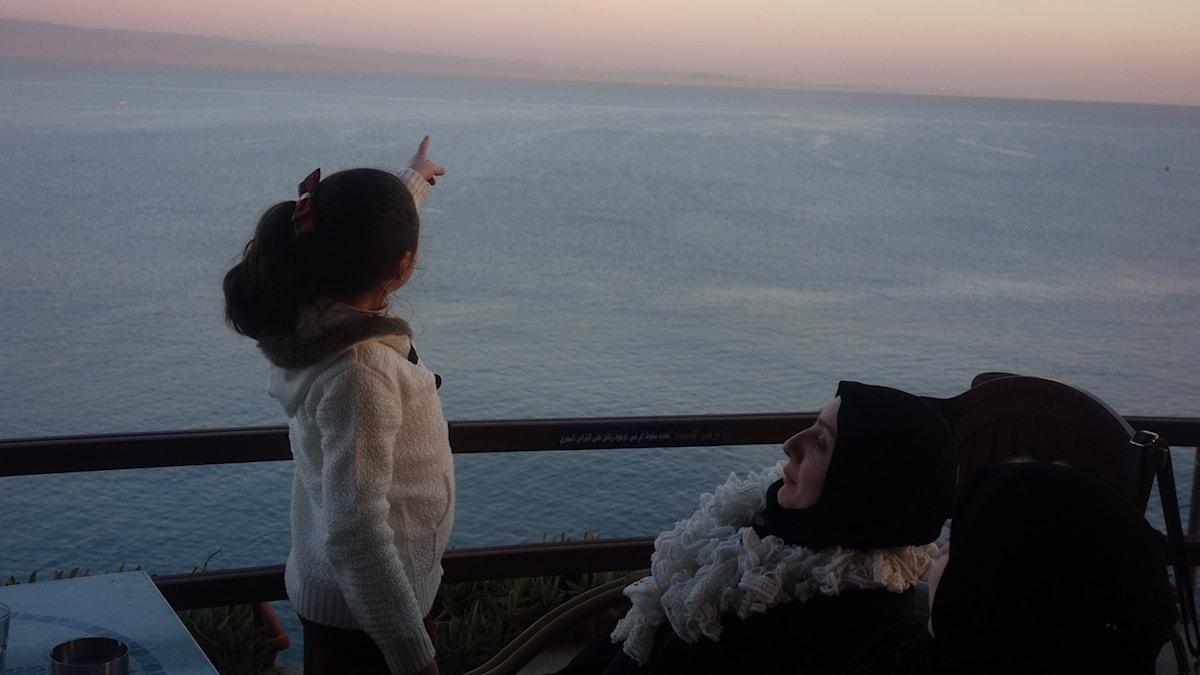 En flicka med havet i bakgrunden pekar mot himlen. En kvinna i svart slöja sitter bredvid.