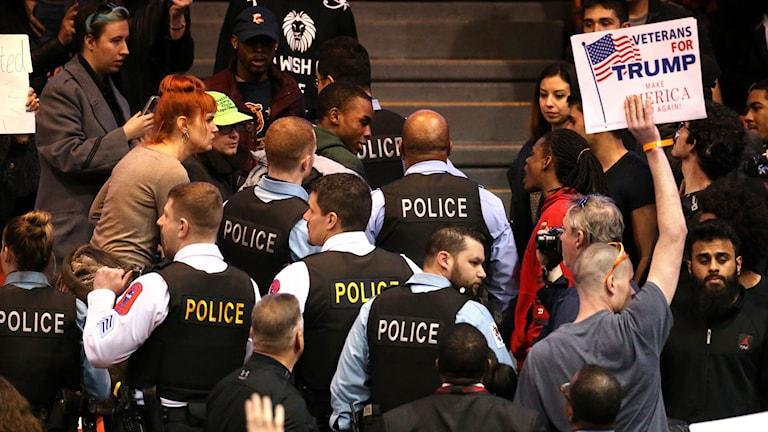 Poliser försöker skapa ordning vid storbråket vid Trumps planerade valmöte, som nuskjuts upp. Foto: Chris Sweda/Chicago Tribune / AP / TT