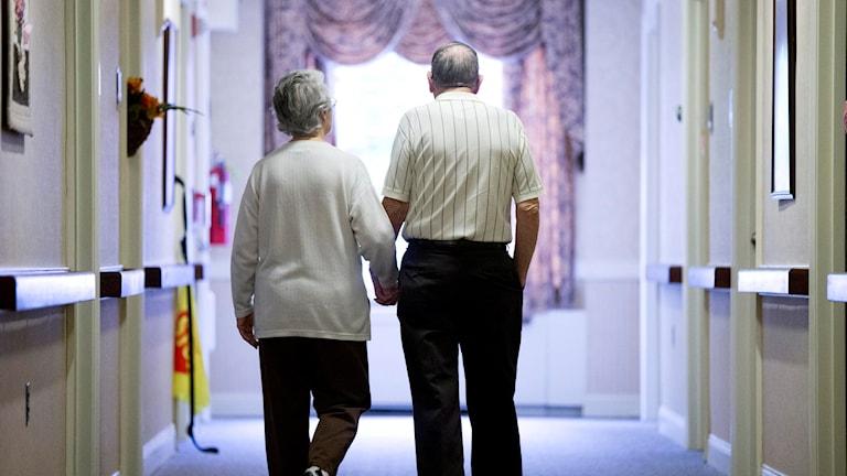 Två äldre människor går hand i hand i en korridor.