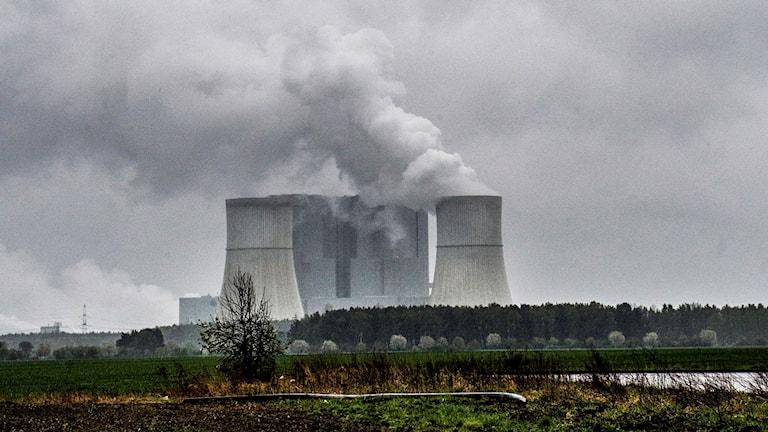 Kolkraftverk som det kommer upp rök ur. Molnig himmel.