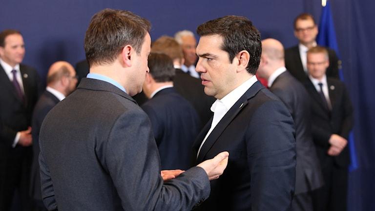 Två män i mörka kostymer pratar med varandra.