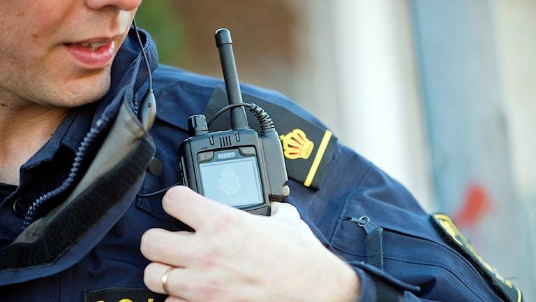En polis med kommunikationsradio på axeln.