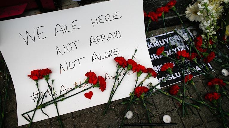 """""""Vi är här, inte rädda, inte ensamma"""", står det på en skylt vid attentatsplatsen."""