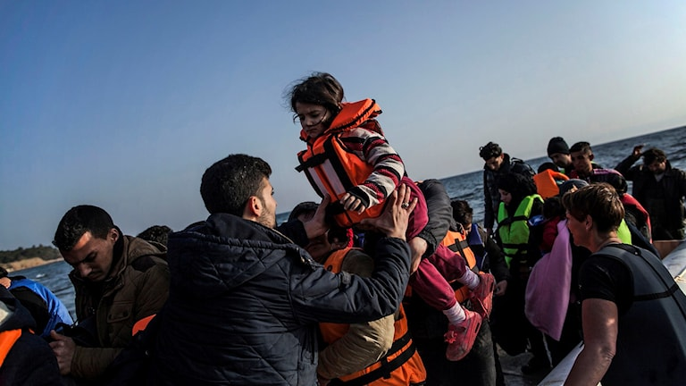 Barn lyfts ur en gummibåt.