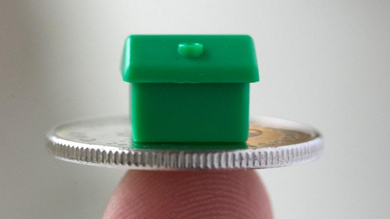 husmodell på mynt balanserar på finger