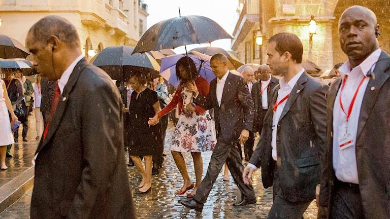 delegation av finklädda människor går genom regnig stad
