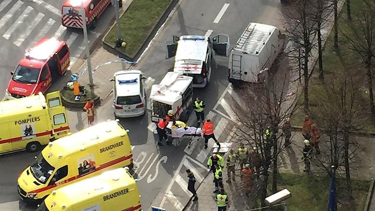 Sjukvårdspersonal evakuerar skadade människor utanför tunnelbanestationen Maalbeek.