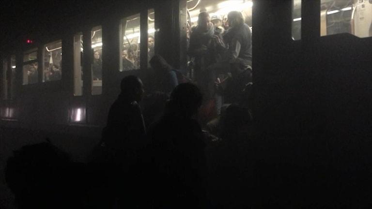Passagerare klättrar ner från en tunnelbanevagn efter explosionen i tunnelbanan i Bryssel.