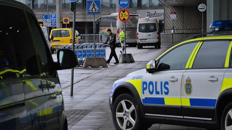 Två polisbilar utanför ankomsthallen på  Arlanda flygplats i Stockholm.