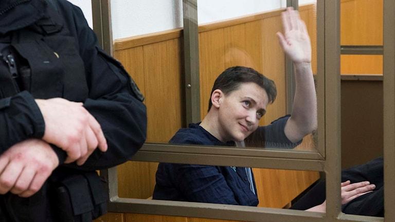 Savtjenko vinkar till journalisterna inifrån en glasbur.