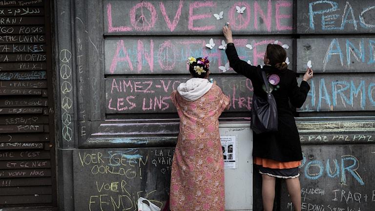 Personer skriver kärlek och fred på väggarna.