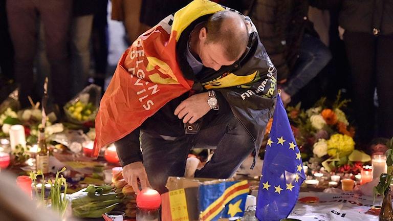 En man, insvept i en flagga, hukar vid en minnesplats i centrala Bryssel för att tända ett ljus.