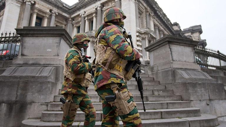 Soldater i kamoflagefärgade uniformer med vapen framför grå byggnad