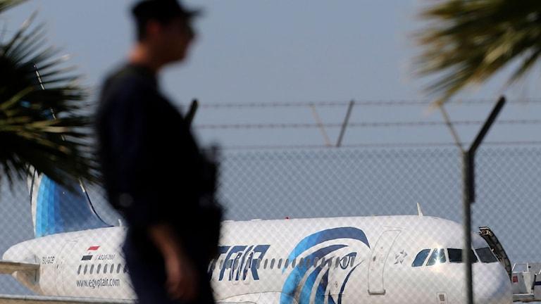 man i profil i förgrunden, palmer och flygplan i bakgrunden
