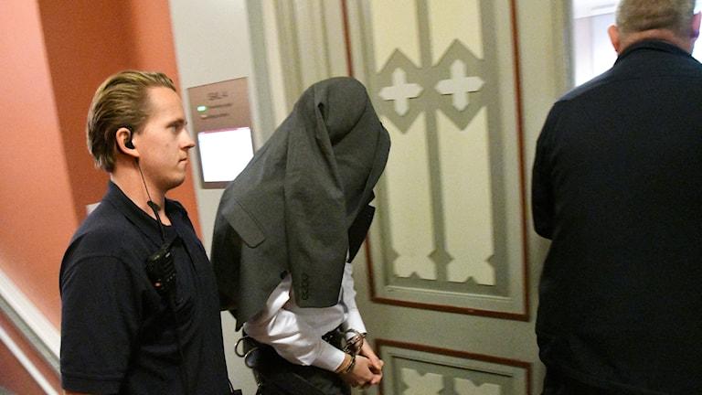 Den huvudåtalade 38-åringen kliver in i rättssalen med kavajen över huvudet.