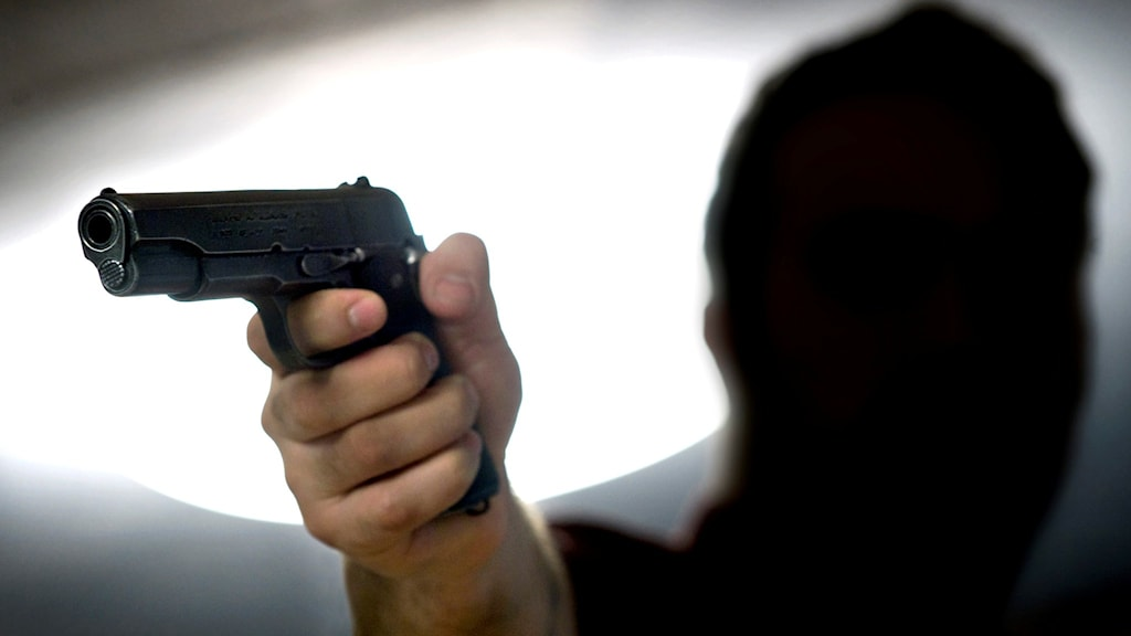 Ett skjutvapen och en man med rånarluva