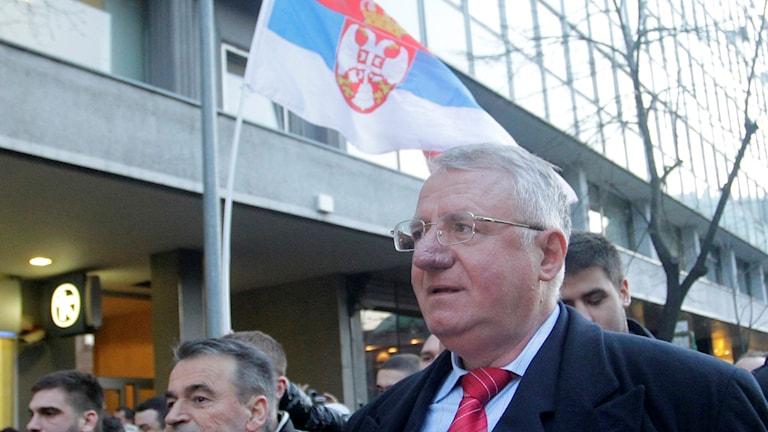 Vojislav Seselj med serbiska flaggan i bakgrunden