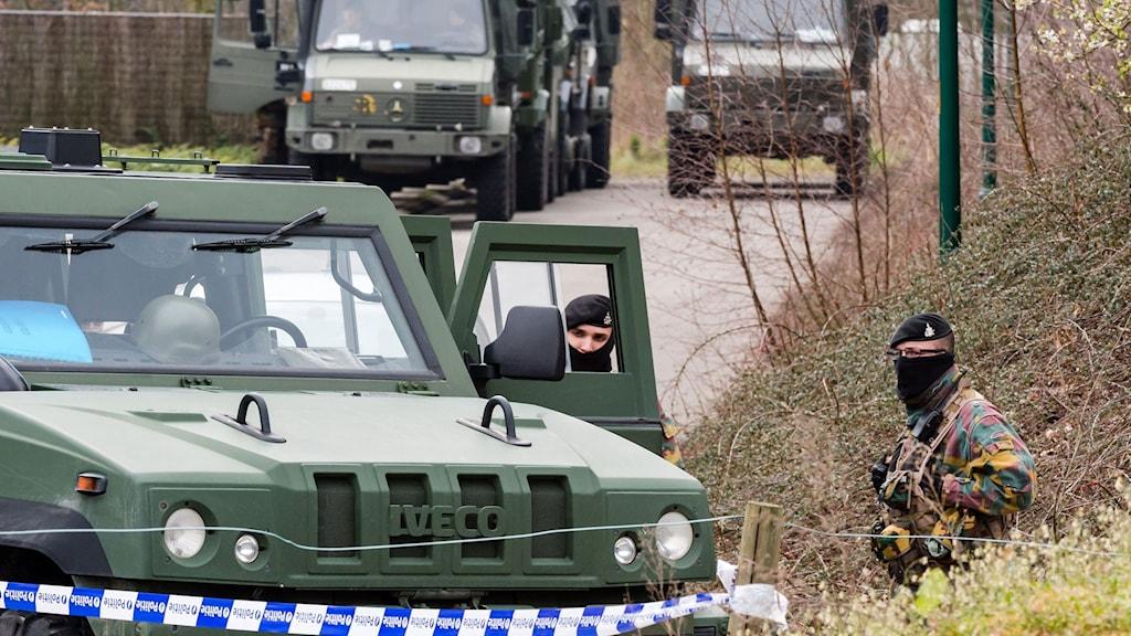 Militärgröna jeepar och maskerade poliser på asfalterad väg
