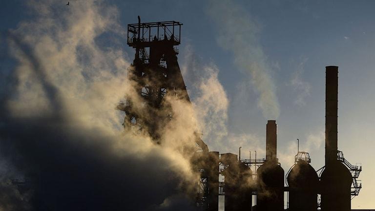 stålverk mot blå himmel mycket rök